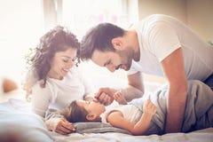 充满敬畏心的 有女儿的父母在床上 免版税图库摄影