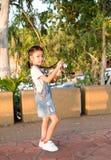 充满旅行,smilling和幸福的亚洲女孩藏品照相机在微明下 免版税库存图片