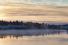 充满活力的日落在湖附近的Inari,芬兰 免版税库存照片