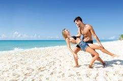 充满爱的愉快的夫妇跳舞在海滩 免版税图库摄影