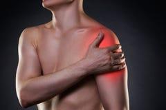 充满痛苦的人在黑背景的肩膀 库存图片