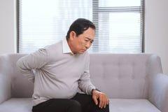 充满痛苦的资深亚裔人在沙发的后面开会 库存照片