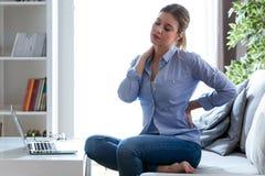 充满肩膀和背部疼痛的疲乏的少妇在家坐长沙发 库存照片