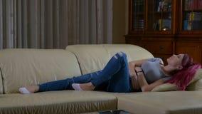充满胃消化不良在家感觉痛苦的学生妇女,她坐长沙发 影视素材