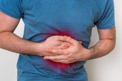 充满胃痛的人握他酸疼的腹部 免版税库存图片