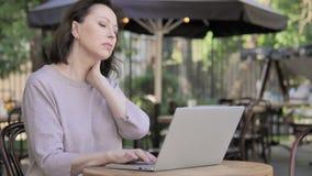 充满脖子痛的老妇人使用室外的膝上型计算机 股票录像