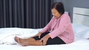 充满腿痛的资深妇女在床上 股票视频