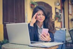 充满运作在咖啡馆的顶头痛苦的年轻女商人 免版税库存照片