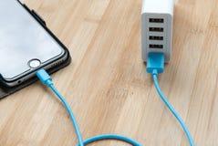 充电一个手机的USB充电器 免版税库存图片