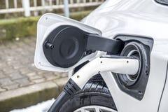 充电一辆的电车的看法和在背景中汽车的一个部份看法 库存图片