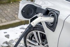 充电一辆的电车的看法和在背景中汽车的一个部份看法 免版税库存照片