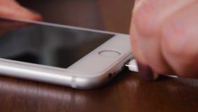 充电与一根充电的绳子的智能手机的特写镜头 插入充电的绳子入智能手机连接器 股票录像