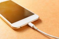 充电与力量银行的智能手机在木委员会 库存图片