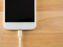 充电与USB缆绳的巧妙的电话 免版税库存照片