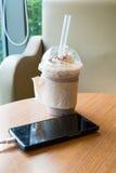充电在咖啡馆的手机与塑料杯子被冰的巧克力frappe 库存图片