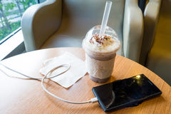 充电在咖啡馆的手机与塑料杯子被冰的巧克力frappe 免版税库存图片