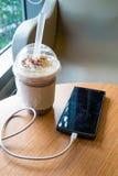 充电在咖啡馆的手机与塑料杯子被冰的巧克力frappe 图库摄影