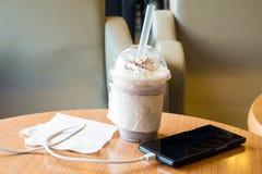 充电在咖啡馆的手机与塑料杯子被冰的巧克力frappe 免版税库存照片