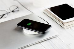 充电在无线充电器新技术的电话 免版税库存照片