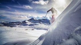 充电在陡坡下的极端滑雪者 免版税库存照片