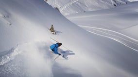 充电在陡坡下的极端滑雪者 库存图片