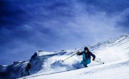 充电在陡坡下的极端滑雪者 库存照片