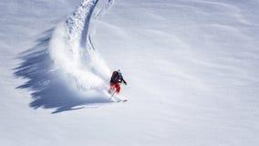 充电在陡坡下的极端滑雪者 免版税库存图片