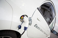 充电电室外白色的汽车 免版税库存图片