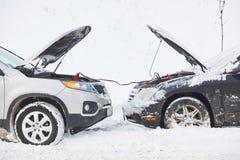 充电的汽车由助推器跨接电线释放了电池在冬天 免版税库存图片
