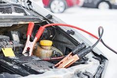 充电的汽车由助推器跨接电线释放了电池在冬天 库存图片