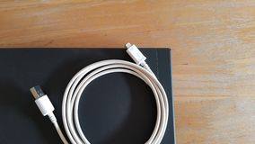 充电的绳子和膝上型计算机 免版税库存照片