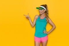 充满活力体育衣裳指向的微笑的妇女 免版税库存照片