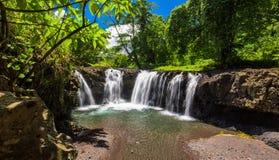 充满活力的Togitogiga下跌与在乌波卢岛,萨摩亚的供游泳的深水潭 免版税图库摄影