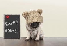 充满坏星期一早晨心情的逗人喜爱的哈巴狗小狗,坐在与文本愉快的星期一的黑板标志旁边,拷贝空间 免版税库存照片