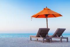 充满太阳床和松弛心情的美好的海滩日落 图库摄影