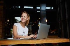 充满好心情的华美的快乐的妇女自由职业者使用距离工作的便携式计算机在咖啡馆酒吧的午餐期间 库存照片