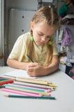 充满热情的六岁的女孩画在第二等的火车支架的铅笔 免版税库存照片