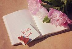 充满爱 在白色卡片的两心脏题字& x22的; love& x22;并且花束桃红色牡丹 免版税库存图片