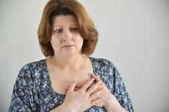 充满痛苦在胸口,咽喉痛的妇女 库存图片