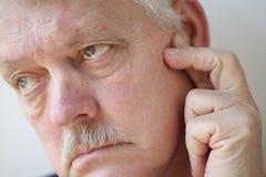 充满痛苦的人在他的耳朵附近 免版税库存图片