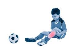 充满痛苦的青年亚裔足球运动员在腿 充分机体 免版税库存照片