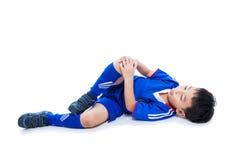 充满痛苦的青年亚裔足球运动员在膝盖关节 充分机体 免版税库存图片