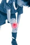 充满痛苦的青年亚裔足球运动员在膝盖 隔绝在白色b 免版税库存图片