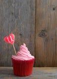 充满糖果心脏爱u的桃红色杯形蛋糕 免版税图库摄影