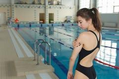 充满肩膀痛苦的游泳者运动员在游泳站立近的游泳池边的片刻前 免版税图库摄影