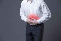 充满胃肠痛苦,在灰色背景的肚子疼的人 免版税库存图片