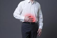 充满胃肠痛苦,在灰色背景的肚子疼的人 免版税库存照片