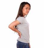 充满背部疼痛的亚洲迷人的少妇 免版税图库摄影
