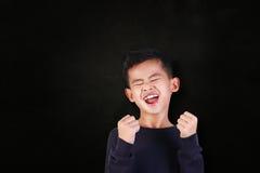 充满胜利喜悦的愉快的学生男孩呼喊  免版税库存图片