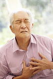 充满胸口痛的资深亚裔人 库存照片